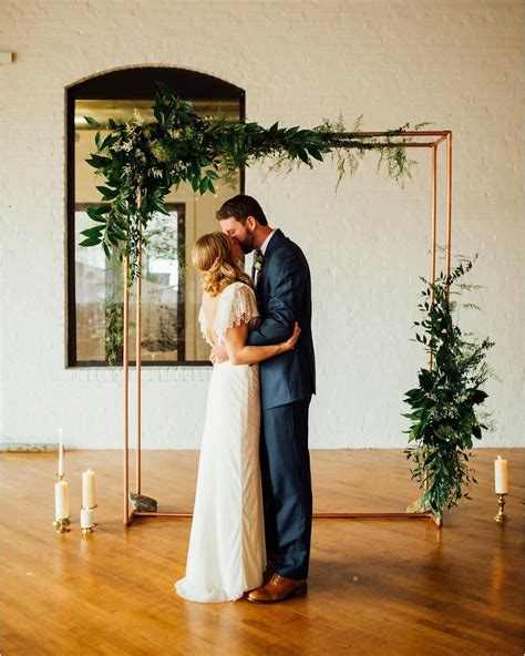 diy copper piping ceremony backdrop with greenery