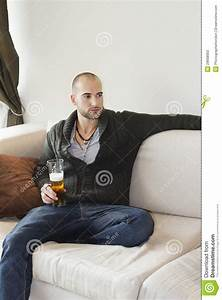 Young Man Sitting Comfortably On Sofa Holding A Drink ...