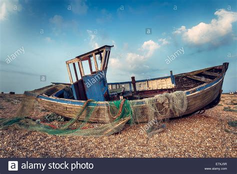 Old Boat Washed Up old wooden fishing boat washed up on a shingle beach stock