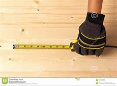 Human Hand Taking Measurement On A Block Of Wood Royalty