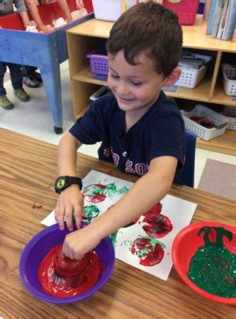 preschool programs amp daycare services at ngcc hopkinton 928 | preschool boy painting with an apple at next generation childrens centers hopkinton ma 333x450