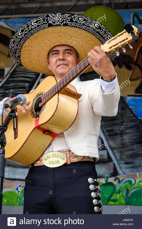 male mexican mariachi acoustic guitar player wearing