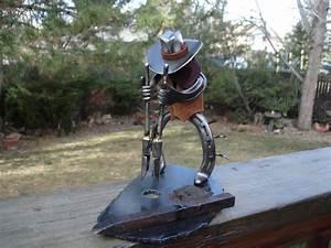 Horseshoe cowboy sculpture digging posthole
