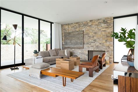 Ambient lighting sets a cozy ambiance contemporary living room with a sleek fireplace and a gray sofa supported by glass legs. Imaginative Décor and Accessories Sparkle at Lindhurst Residence in Texas