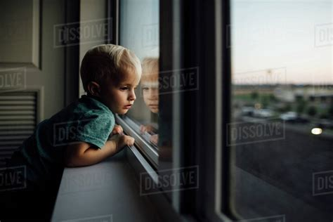 Through Child by Side View Of Baby Boy Looking Through Window While