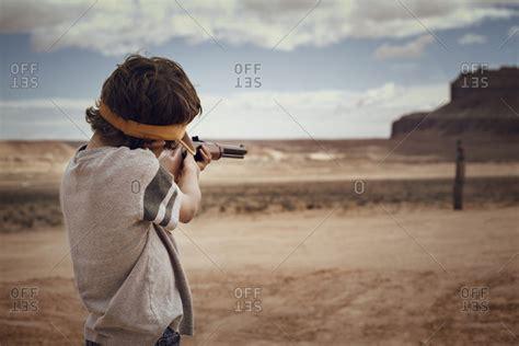 boy aiming rifle  standing  field  sky stock