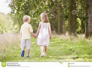 Two Young Children Walking On Path Holding Hands Stock ...