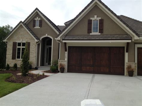like exterior colors wood garage door no visible hardware and wood shutters exterior