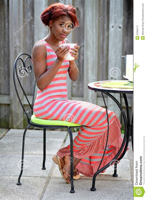 young black woman enjoying coffee   patio royalty