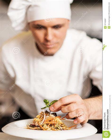 chef decorating pasta salad  herbal leaves stock image