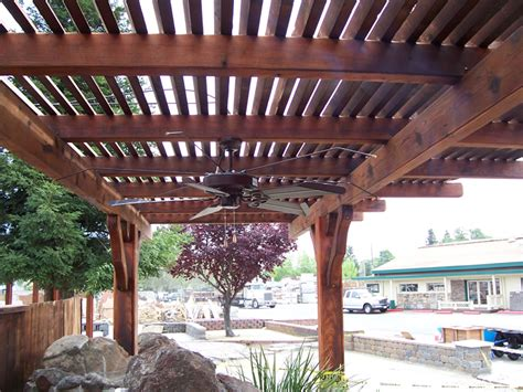 wood finish lattice patio cover with ceiling fan in