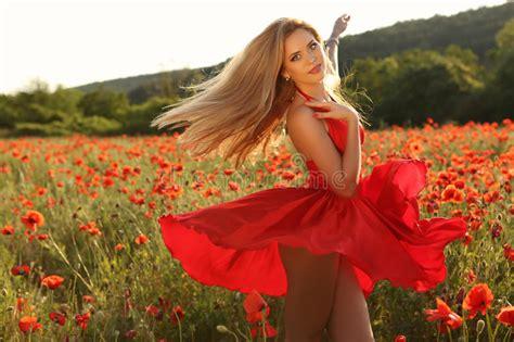 Blond Girl In Elegant Dress Posing In Summer Field Of Red