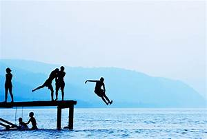 Silhouettes of Kids Jumping Off Dock