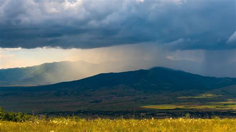 beautiful dramatic landscape storm heavy rain sun beams