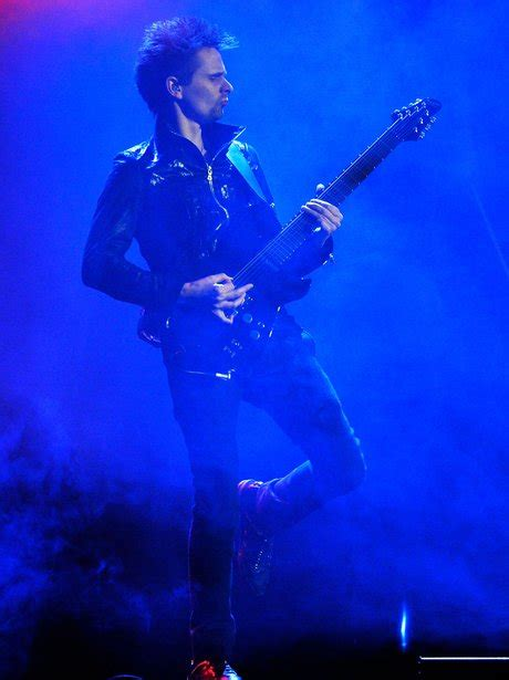 Muse frontman Matt Bellamy wields his guitar on stage at ...