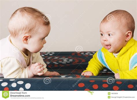 Two Babies Crawling On A Sofa Royalty Free Stock Images