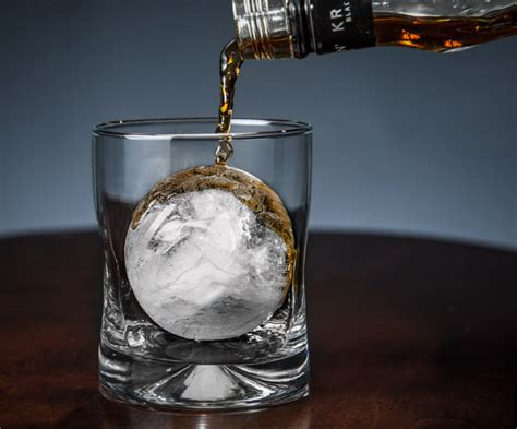 cube mold pouring whiskey onto a large