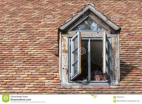 wohngemeinschaften auf alten bauernhöfen offenes fenster in einem alten mansardenfenster auf einem dach mit historischem stockfoto bild