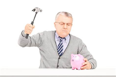Angry Mature Man Trying To Break A Piggy Bank With A