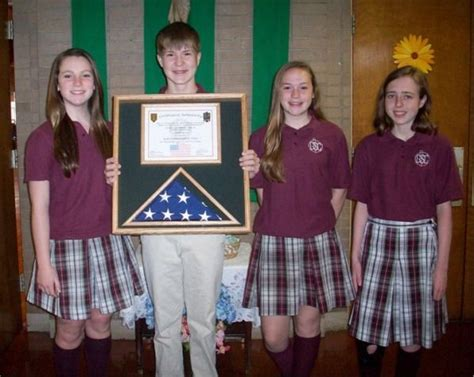 This custom flag display case features the american flag and the certificate. Claire Fleck, left; Eddie Wagner; Colleen McDermott; and ...
