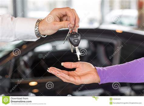 Car Salesman Handing Over Car Keys In Dealership Stock