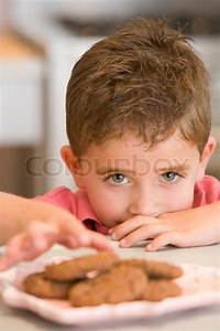 Boy taking biscuit from plate | Stock Photo | Colourbox