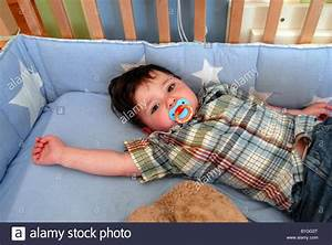 One and 1/2 year old Hispanic American boy in his crib ...