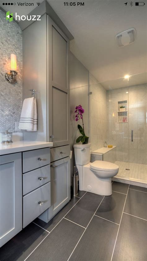 bathroom dark grey tile flooring light grey cabinets