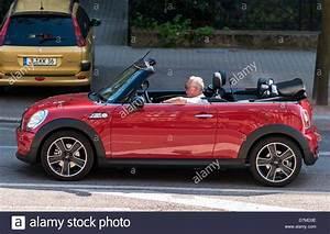 Elderly Man Driving A Red Mini Cooper Convertible Car
