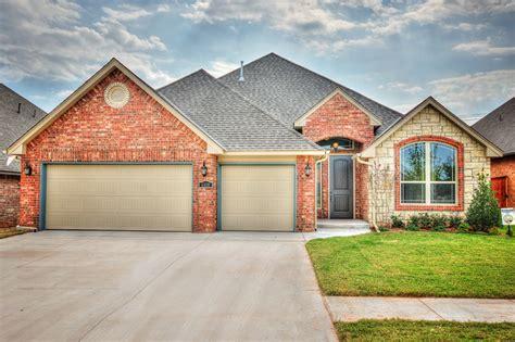 3 car garage with brick exterior transitional