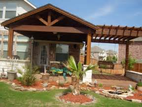 outdoor covered patio with a stone fireplace and niche for