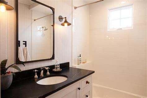 white pedestal sink with aged brass rivet mirror