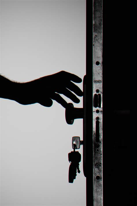 silhouette photo  person holding door knob  stock
