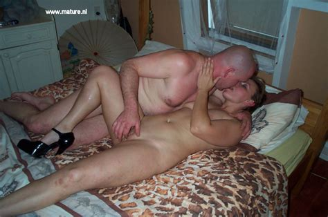 mature couple at play on their bed