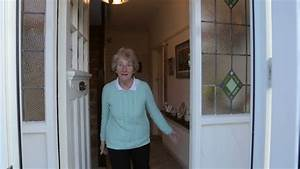 Senior woman opens front door and welcomes… - Royalty Free ...