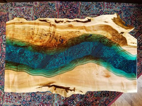A classic table filled with epoxy resin for a natural flowing look. Winding river custom epoxy table   Live edge wood table, Blue coffee tables, Amazing resin