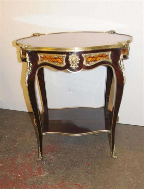 A gorgeous french empire style coffee or cocktail table by baker furniture usa, late 20th century cherry wood top, with burled walnut banding and legs and ebonized feet and accents. French Empire Side Table Cocktail Centre Tables