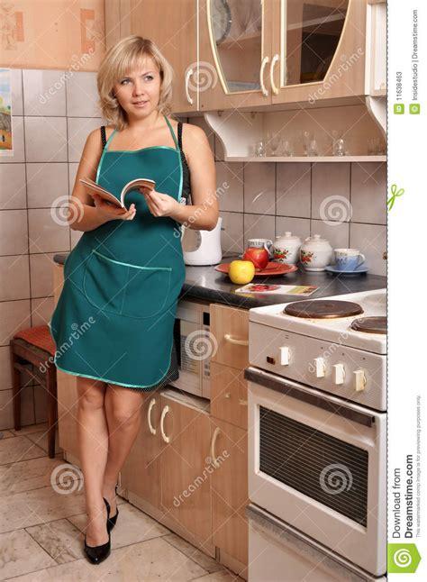 femme a la cuisine la femme au foyer dans le tablier vert sur la cuisine