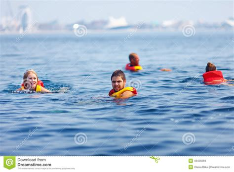 Sink Or Swim Download by People In Lifejackets Swimming In Open Sea Stock Image