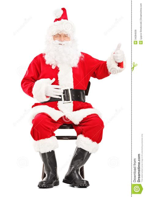 happy santa claus sitting on a wooden chair and giving a