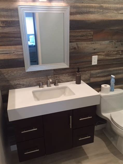 bathroom with floating vanity and wood tile wall ateam