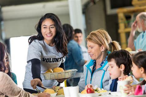 volunteer serves meal  homeless  shelter stock photo