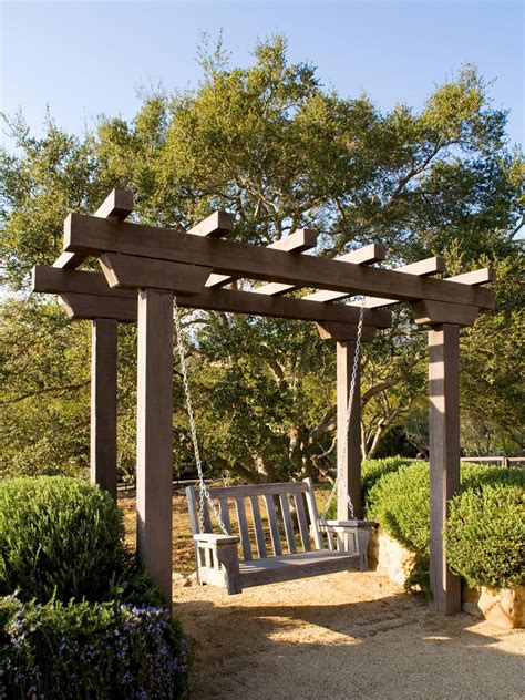 arbor backyard a lovely wooden arbor with attached swing is bordered by ornamental shrubs in raised garden beds