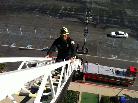 Climbing a 100 ft. aerial ladder to the roof of The ...