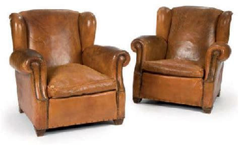 a pair of brown distressed leather club chairs second