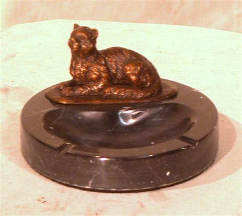 bronze cat figurine lying  marble ashtray