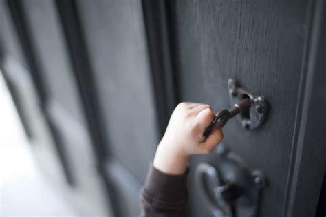 unlock the door child reaching up to unlock an wooden door 7250
