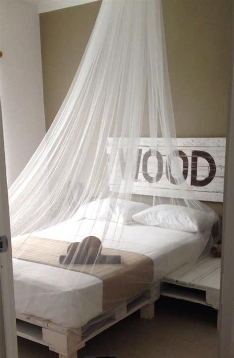 una cama hechas enteramente de tarimas con su cabecera
