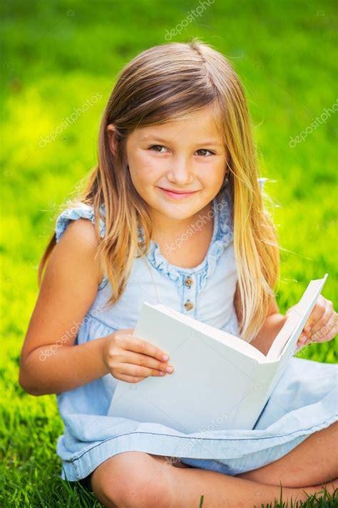 Little girl reading book outside — Stock Photo