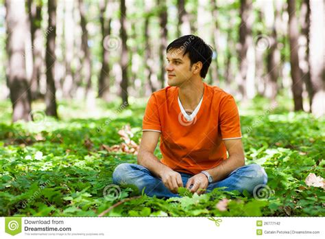 Handsome Man Sitting Crosslegged In The Woods Stock Photo